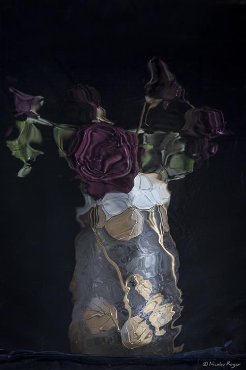 Reflet d'un vase de fleurs déformé par les mouvements de l'eau