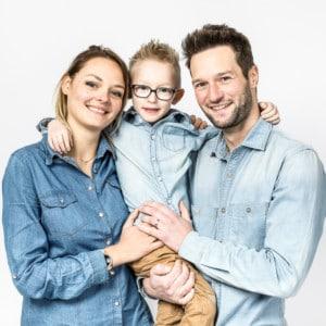 Photographie d'une famille avec leur jeune enfant dans les bras.