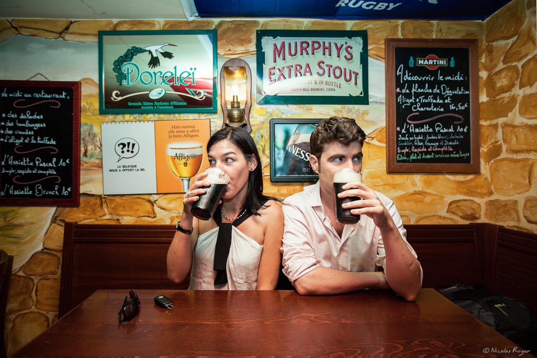 Photographie d'un couple dans un pub, une image décalée prise dans l'amusement d'une séance en ville.