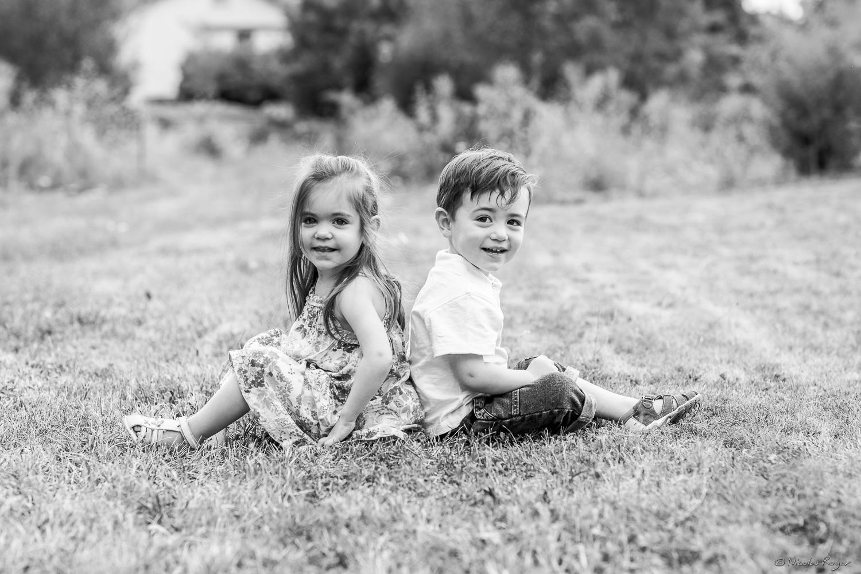 Image d'un frère et une soeur dos à dos dans un jardin.