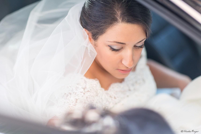 Photographie de la mariée dans la voiture vers le mariage