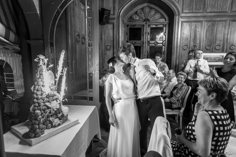 Baiser des mariés devant le gâteau