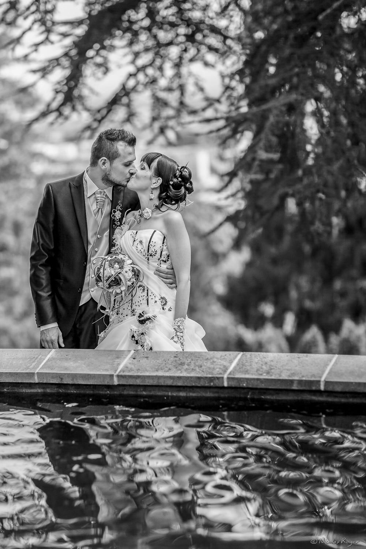 Baiser des mariés devant un bassin